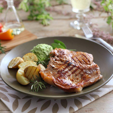 Delicious pork chops with roast potatoes and mashed green peas